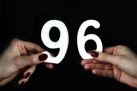 On a black background, female hand with numbers ninety-six. Imagens
