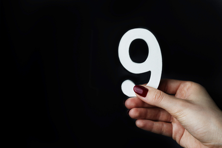 On a black background, female hand with number nine.