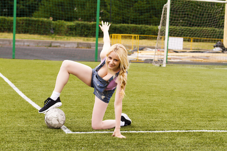Blonde girl with a ball sitting on a football field on a Sunny summer day.