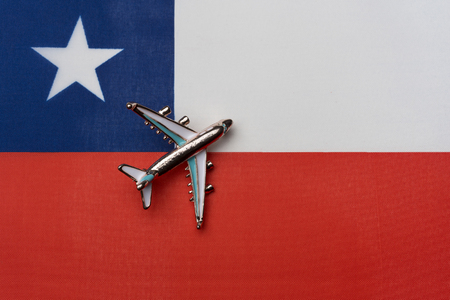 Plane over the flag of Chile, the concept of journey. Toy plane on the flag as a background.