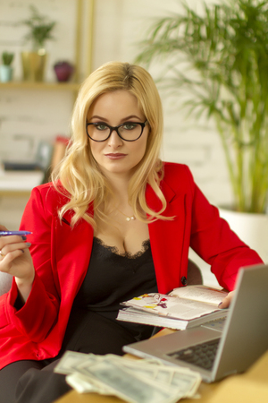 Beautiful blonde business lady working at home on a laptop. Business concept at home.