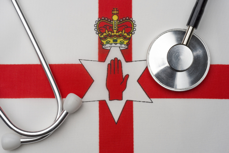 Northern Ireland flag and stethoscope. The concept of medicine. Stethoscope on the flag in the background.