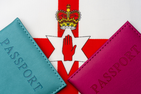 Against the flag of Northern Ireland is a passport. The concept of travel and tourism.