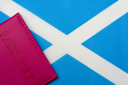 Against the flag of Scotland is a passport. The concept of travel and tourism.