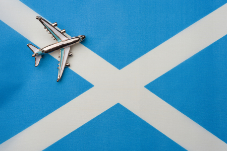 Plane over the flag of Scotland the concept of a travel Toy plane on the flag in the background. Фото со стока
