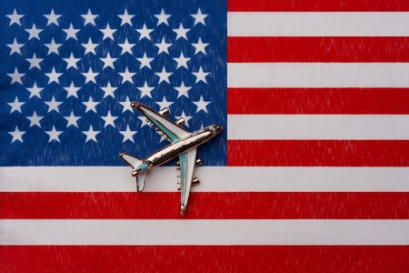 Airplane over the flag Small Pacific remote Islands of the United States concept of traveling abroad Toy airplane on the flag as the background.