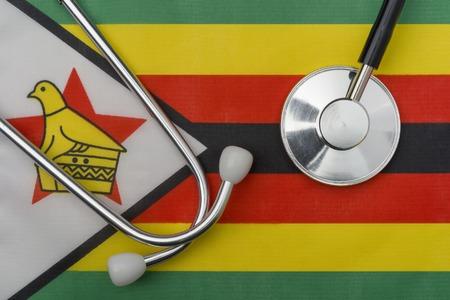 Zimbabwe flag and stethoscope. The concept of medicine. Stethoscope on the flag in the background.