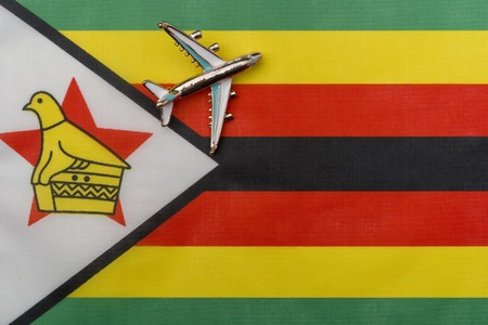 Plane over the flag of Zimbabwe the concept of the journey. Toy plane on the flag in the background.