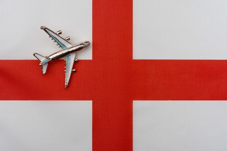 Plane over the flag of the English Kingdom travel concept. Toy plane on the flag in the background.