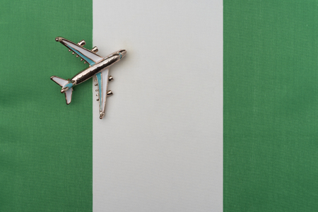 Plane over the flag of Nigeria travel concept. Toy plane on the flag in the background.