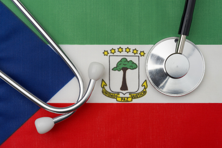 Equatorial Guinea flag and stethoscope. The concept of medicine. Stethoscope on the flag in the background.