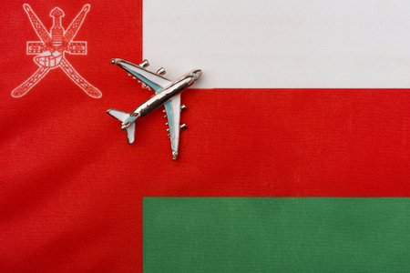 Plane over the flag of Oman travel concept. Toy plane on the flag in the background.