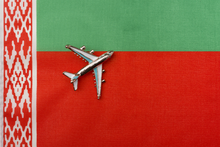 Plane over the flag of Belarus travel concept. Toy plane on the flag in the background.