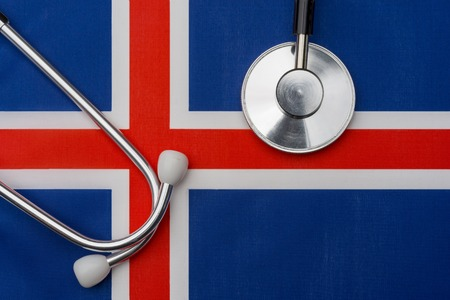 Iceland flag and stethoscope. The concept of medicine. Stethoscope on the flag in the background. Stock Photo