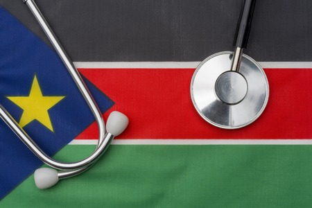 South Sudan flag and stethoscope. The concept of medicine. Stethoscope on the flag in the background.