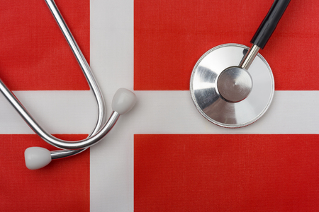 Danish flag and stethoscope. The concept of medicine. Stethoscope on the flag in the background.