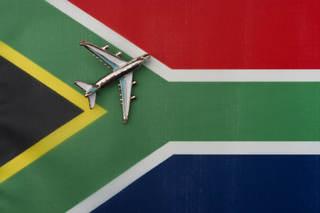 Airplane over South African flag travel and tourism concept. Toy plane on the flag in the background.