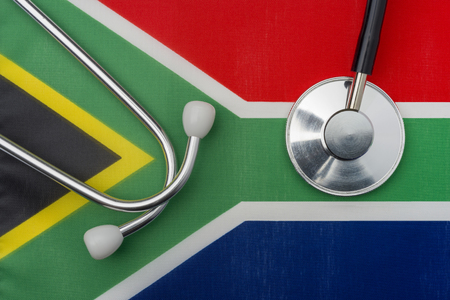 South African flag and stethoscope. The concept of medicine. Stethoscope on the flag in the background. Stock Photo