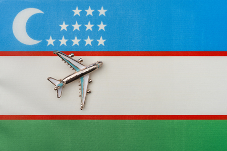 Plane over the flag of Uzbekistan the concept of travel and tourism. Toy plane on the flag in the background.
