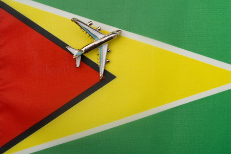 Plane over the flag of Guyana, the concept of travel and tourism. Toy plane on the flag in the background.