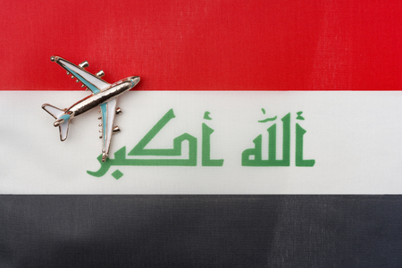 Plane over Iraq flag travel concept. Toy plane on the flag in the background.