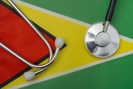 Guyana flag and stethoscope. The concept of medicine. Stethoscope on the flag in the background.