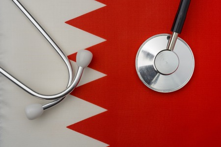 Bahrain flag and stethoscope. The concept of medicine. Stethoscope on the flag in the background. Фото со стока