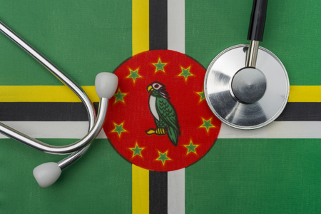 Dominica flag and stethoscope. The concept of medicine. Stethoscope on the flag in the background.