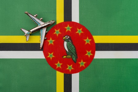 Plane over the flag of Dominica concept of travel and tourism. Toy plane on the flag in the background.