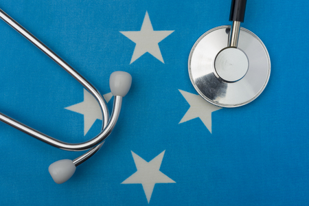 Flag of Micronesia and the stethoscope. The concept of medicine. Stethoscope on the flag in the background.