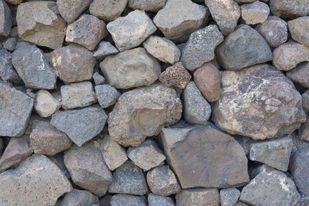 Texture of stones and cobblestones with sharp edges. Natural stones laid in the wall.
