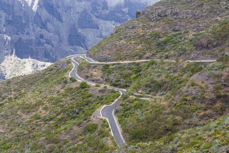 Mountain road on the island of Tenerife, high mountains and dense forests. The concept of tourism and recreation.