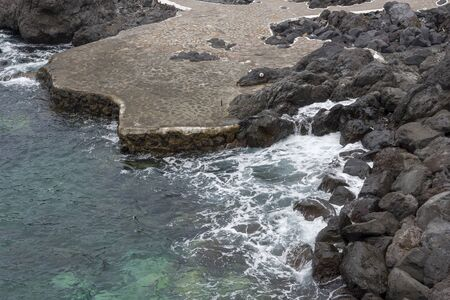 Coastline with stones on the island of Tenerife. The concept of tourism and recreation.