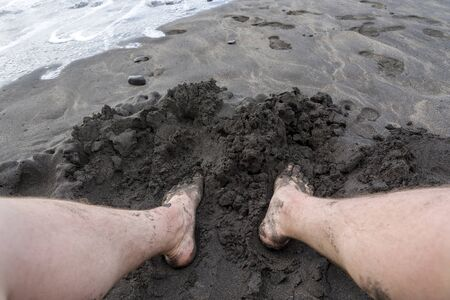 Men's feet in black sand on the beach of Tenerife. The concept of recreation and tourism. Standard-Bild - 129122888