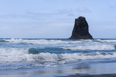 Black sand beach in Spain on the island of Tenerife. The concept of tourism and outdoor recreation.