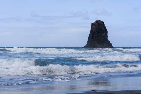 Playa de arena negra en España en la isla de Tenerife. El concepto de turismo y recreación al aire libre.