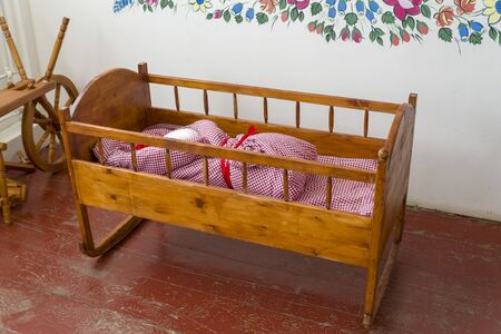 Children's wooden cot for infants in the room. The concept of home decor children's room. Archivio Fotografico