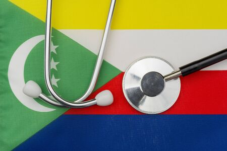 Flag of Comoros and stethoscope. The concept of medicine. Stethoscope on the flag in the background.