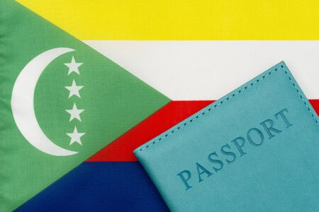 Against the background of the flag of Comoros is a passport. The concept of travel and tourism.