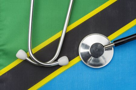 Tanzania flag and stethoscope. The concept of medicine. Stethoscope on the flag in the background.