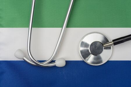 Sierra Leone flag and stethoscope. The concept of medicine. Stethoscope on the flag in the background.