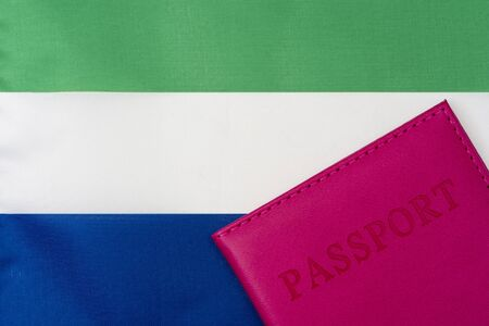 On the background of the flag of Sierra Leone is a passport. The concept of travel and tourism. 写真素材