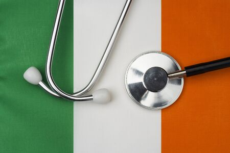 Irish flag and stethoscope. The concept of medicine. Stethoscope on the flag in the background.