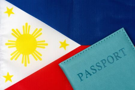 Against the background of the flag of the Philippines is a passport. The concept of travel and tourism.