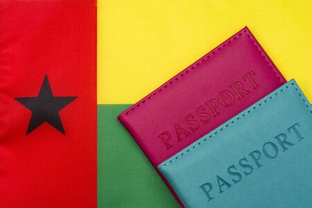 Against the background of the flag of Guinea-Bissau is a passport. The concept of travel and tourism. 写真素材