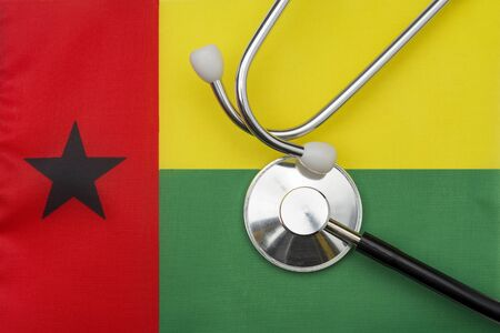Guinea-Bissau flag and stethoscope. The concept of medicine. Stethoscope on the flag in the background.
