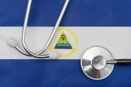 Nicaragua flag and stethoscope. The concept of medicine. Stethoscope on the flag in the background.