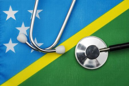 Solomon Islands flag and stethoscope. The concept of medicine. Stethoscope on the flag in the background. Zdjęcie Seryjne