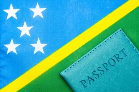 Against the background of the flag of the Solomon Islands is a passport. The concept of travel and tourism.
