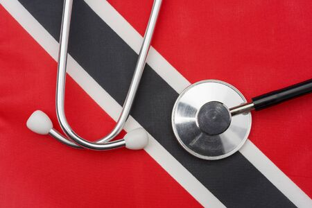 Flag of Trinidad and Tobago and stethoscope. The concept of medicine. Stethoscope on the flag in the background. Zdjęcie Seryjne